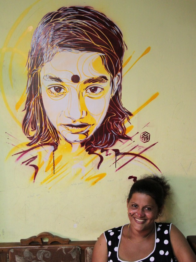 Kanchana with C215's art on her living room wall